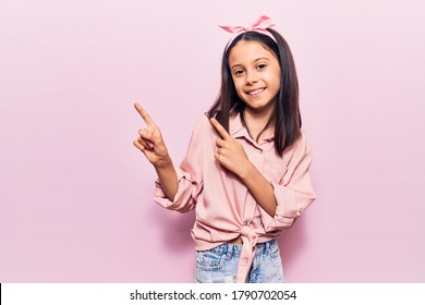 Beautiful child girl wearing casual clothes smiling and looking at the camera pointing with two hands and fingers to the side.