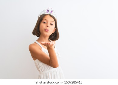 Beautiful child girl wearing princess crown standing over isolated white background looking at the camera blowing a kiss with hand on air being lovely. Love expression.
