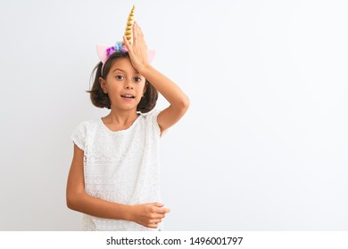 Beautiful child girl wearing unicorn diadem standing over isolated white background surprised with hand on head for mistake, remember error. Forgot, bad memory concept.