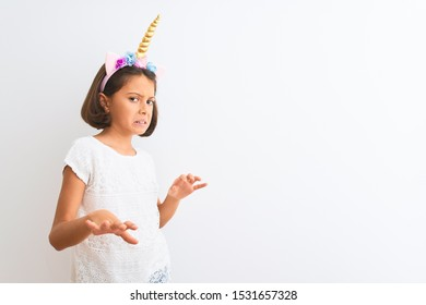 Beautiful child girl wearing unicorn diadem standing over isolated white background disgusted expression, displeased and fearful doing disgust face because aversion reaction. With hands raised. Annoy