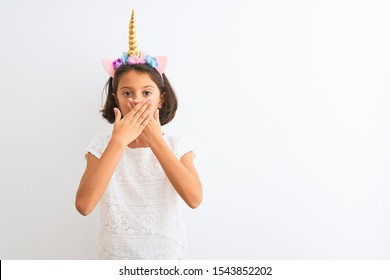 Beautiful child girl wearing unicorn diadem standing over isolated white background shocked covering mouth with hands for mistake. Secret concept.