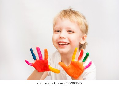 Beautiful child with hands in paint. Portrait of laughing kid. Close up of cheerful funny small boy isolated on white background. Blond baby boy portrait ready to make handprints. Lifestyle concept.