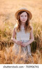 Beautiful child play a field of wheat