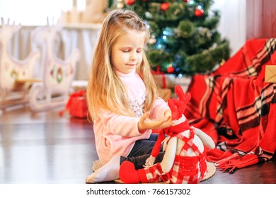 Beautiful child plays a toy in the living room. Concept New Year, Merry Christmas, holiday, vacation, winter, childhood.