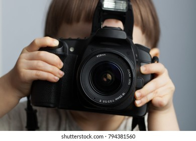 Beautiful child in with professional camera. Little boy with long blond hair photographing in the Studio.