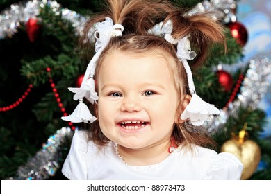 Beautiful child sitting against Christmas decoration.