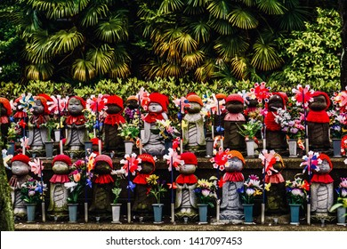 "Beautiful child statues. Row of small monk statues in the park. The children guardian called ""Jizo"", They are dressed by red hat, red apron and a windmill, seen in temples or shrines throughout Japan."