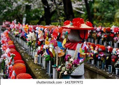 "Beautiful child statues. Row of small monk statues. The children guardian called ""Jizo"", They are dressed by red hat, red apron and hold a windmill, seen in temples or shrines throughout Japan."