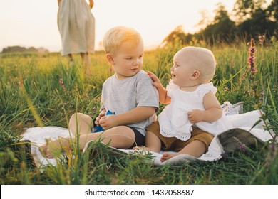 Beautiful children playing on nature outdoors. Brother and sister at summer on sunset. Baby girl and child boy are having picnic on green nature background. Photo of family values, happy childhood