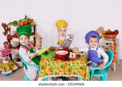 beautiful children prepare in kitchen.  little cute children in costume of Cook. funny cooks with vegetables in studio