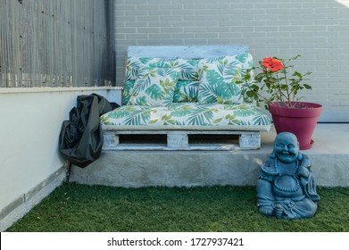 Beautiful Chillout Decoration Composed Of A Sofa Made With Wooden Pallets A Hibiscus And A Smiling Buddha. September 28, 2019. Madrid. Spain. Relax Decoration yoga taichi