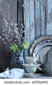 Beautiful china, vintage porcelain tea cups, saucers, branches of willow in glass vase, vintage metal tea pot, set of old metal plates, fresh hellebore on aged, weathered wooden background, daylight