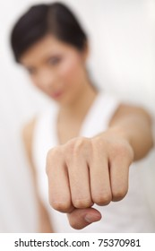 A beautiful Chinese Asian Oriental girl performing a martial arts fist punch to the camera, the focus is on her fist