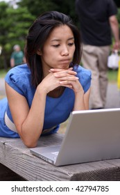 Beautiful Chinese in blue dress working on a laptop outside on a bench