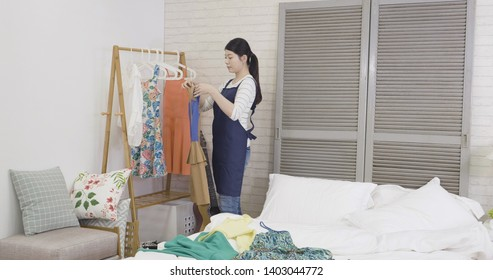 beautiful chinese housewife helping daughter cleaning up her bedroom at home in day time. young mom in apron hanging dress on hanger putting on clothing rack from messy bed with white sheet.
