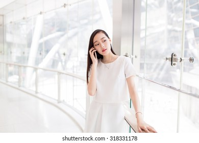 beautiful chinese rapunzel, wearing a white dress, standing alone glazing mall