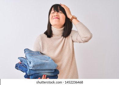 Beautiful Chinese shopkeeper woman holding folded jeans over isolated white background stressed with hand on head, shocked with shame and surprise face, angry and frustrated. Fear and upset