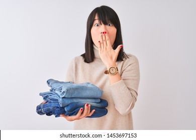 Beautiful Chinese shopkeeper woman holding folded jeans over isolated white background cover mouth with hand shocked with shame for mistake, expression of fear, scared in silence, secret concept