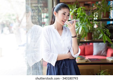 beautiful chinese woman in the coffee shop, using their mobile phone