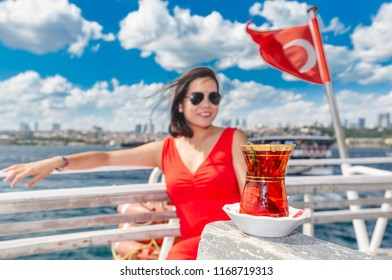 Beautiful Chinese woman cruises on ferry with Turkish flag and tea view in Istanbul,Turkey