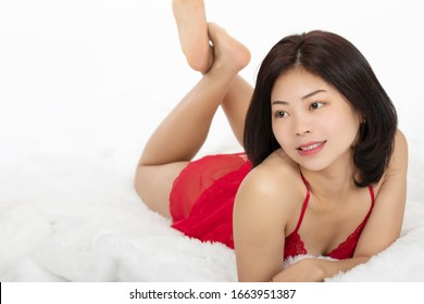 Beautiful Chinese woman dressed in a red thong isolated on a white background