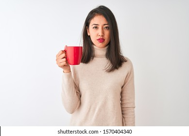 Beautiful chinese woman drinking red cup of coffee standing over isolated white background with a confident expression on smart face thinking serious