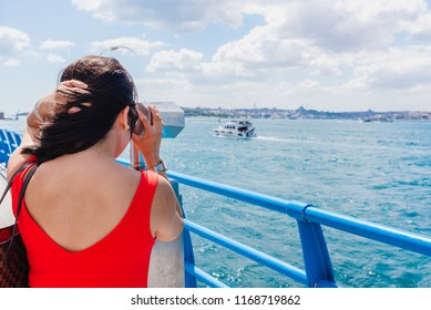 Beautiful Chinese woman looks through sightseeing binoculars on Bosphorus,a popular destination in Istanbul,Turkey