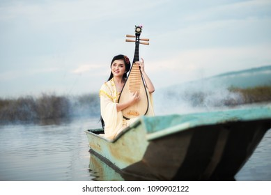 Beautiful Chinese woman sitting and playing the traditional Chinese musical instrument ( pipa) Boats on the lake