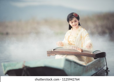 Beautiful Chinese woman sitting and playing the traditional Chinese musical instrument Boats on the lake