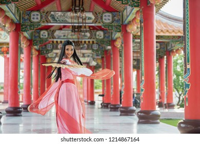 Beautiful Chinese woman with a traditional suit with blow in her hands, Beautiful and belligerent face, Young Samurai. woman with holding Chinese blows the weapon of the samurai.