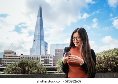Beautiful Chinese woman typing on the phone outdoors
