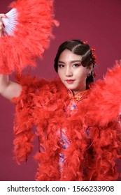 Beautiful Chinese woman wearing red dress holding up red fan with classy make up and hair vintage style on red background, Isolated.
