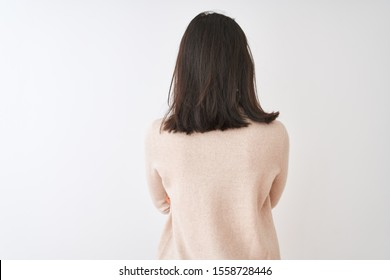 Beautiful chinese woman wearing turtleneck sweater standing over isolated white background standing backwards looking away with crossed arms