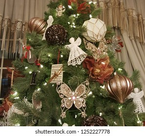Beautiful christmas angel, glittering butterfly, poinsettia, musical instruments, and christmas balls hanging on xmas tree with glowing lights.