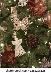 Beautiful christmas angel, glittering butterfly, poinsettia, and christmas balls hanging on xmas tree with glowing lights.