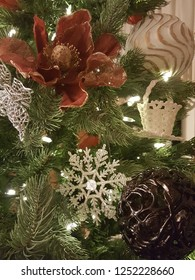 Beautiful christmas angel, glittering snowflake, poinsettia, and christmas balls hanging on xmas tree with glowing lights.