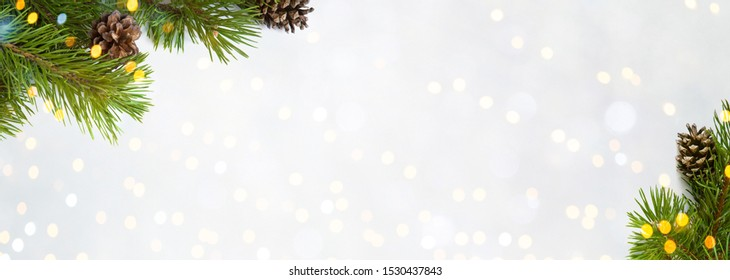 Beautiful Christmas Background with fresh fir tree. Frame of green Spruce branches with cones on light background. Wide Angle Template for design. Panoramic Web banner with copy space