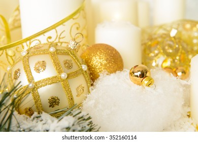 Beautiful Christmas background: golden christmas toys, candles and golden gift box in the snow.