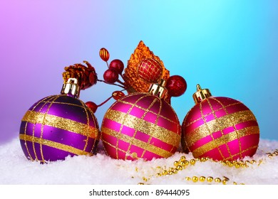 beautiful Christmas balls and cone on snow on bright background