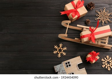Beautiful Christmas composition with miniature sleigh on black wooden table, flat lay. Space for text