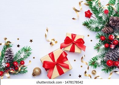 Beautiful Christmas composition on white background with golden Chritmas gift boxes, snowy fir branches, conifer cones, decoration and red berry. Top view.