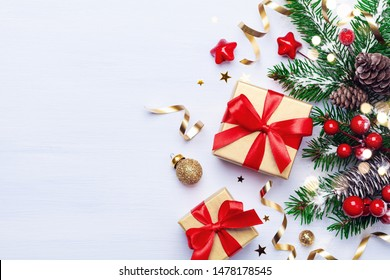 Beautiful Christmas composition on white background with golden Christmas gift boxes, snowy fir branches, conifer cones, holiday decoration and red berry. Top view.