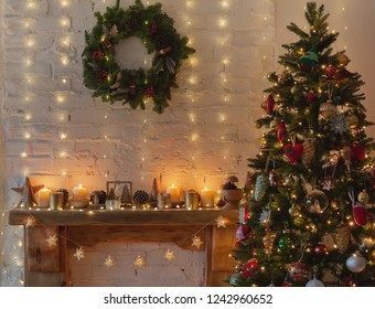 Beautiful Christmas, decorated wood mantelpiece, lit up Christmas tree with baubles and ornaments, stars, wooden decorations, Christams wreath, icicle lights and lit up candles, selective focus