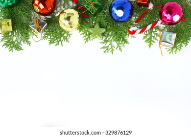 Beautiful Christmas decoration and pine leaves on white background