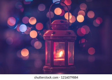 Beautiful Christmas decoration, retro style red lantern with candle inside over festive blurry bokeh background, happy New Year time