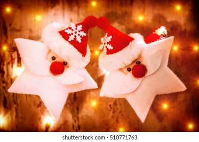 Beautiful Christmas decoration, two Santa Claus toys in a stars shape decorating glowing wooden wall, festive still life