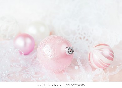 Beautiful Christmas decoration in white and pink colors: several Christmas balls with white ribbon and pearls on a pink lacy background, with space for text