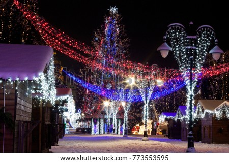 beautiful christmas decorations of a small town with a huge christmas tree in the center
