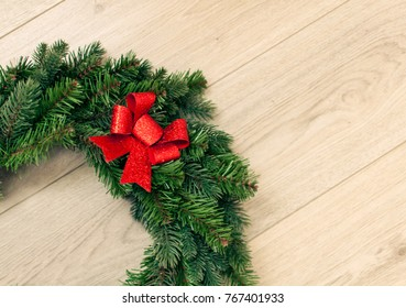 Beautiful Christmas garland with red bow on wooden background, selective focus