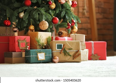 Beautiful Christmas gifts under fir tree on floor in room